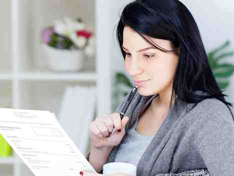 Woman looking at paper bill